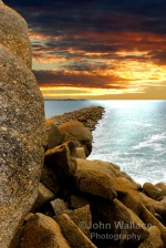 The sun sets spectacularly across the granite breakwater