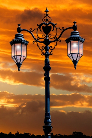 A street lamp standard lights up in preparation for the dark night as the setting sun creates a beautiful sunset