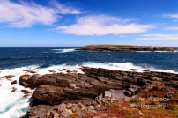 A jagged rocky coastline off the coast of Kangaroo Island, South Australia, the background island is one of 'The Brothers' (Casuarina Islets).