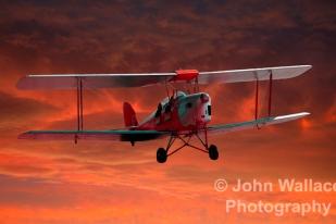 A two seater tigermoth biplane heading homeward